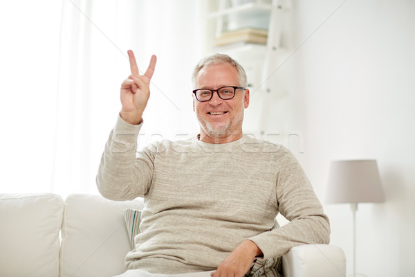 smiling senior man showing v sign at home Stock photo © dolgachov