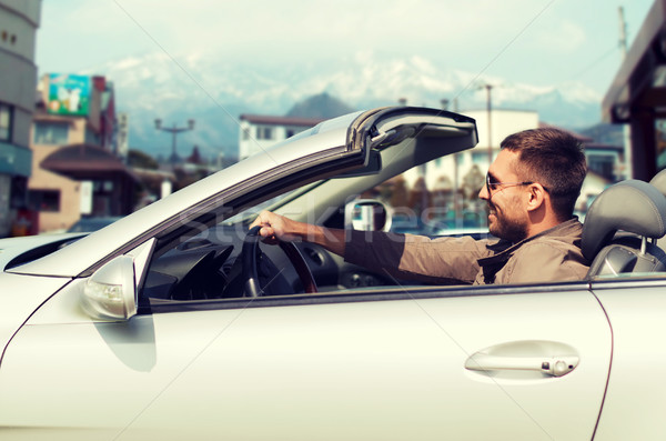 happy man driving cabriolet car over city in japan Stock photo © dolgachov