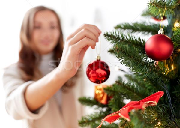 happy young woman decorating christmas tree Stock photo © dolgachov