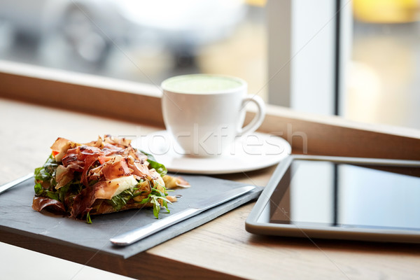 prosciutto ham salad with tablet pc at restaurant Stock photo © dolgachov