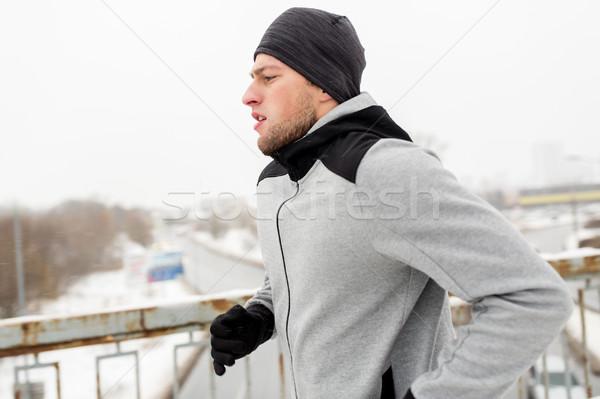 man running along winter bridge Stock photo © dolgachov