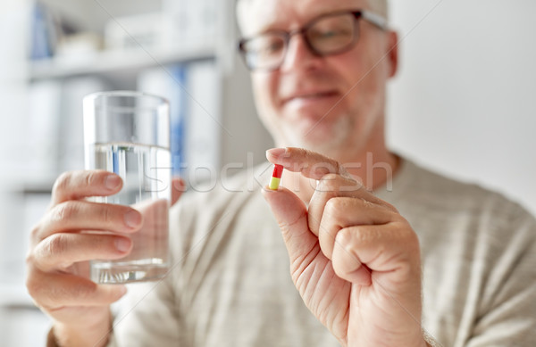 close up of old man hands with pill and water Stock photo © dolgachov