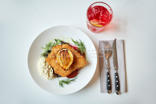 fish salad and glass of drink on restaurant table  Stock photo © dolgachov