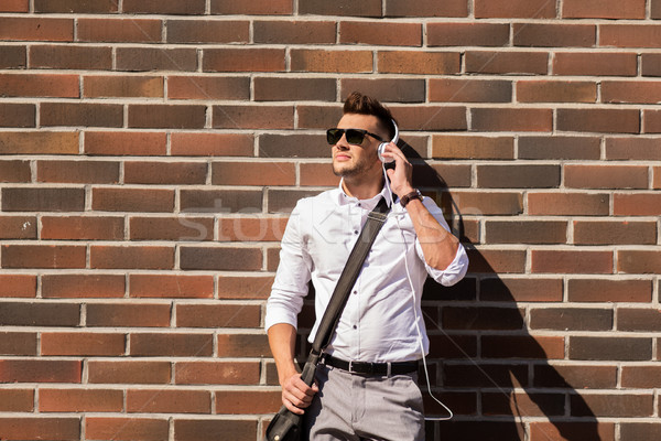 young man in headphones with bag over brickwall Stock photo © dolgachov