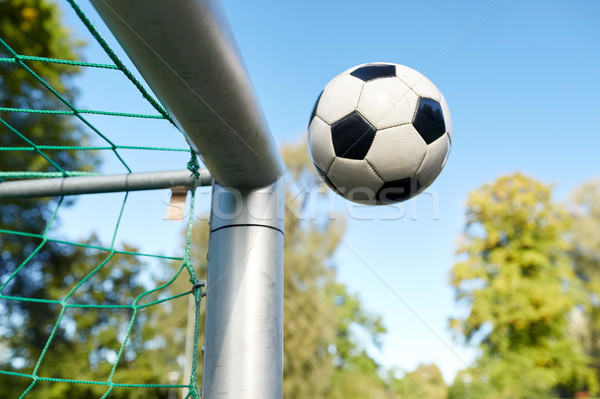 soccer ball flying into football goal net on field Stock photo © dolgachov