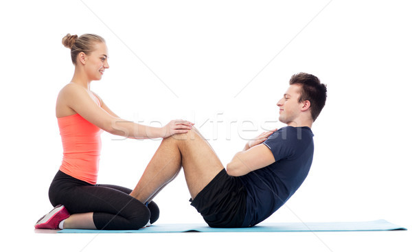 Stock photo: happy sportive man and woman doing sit-ups