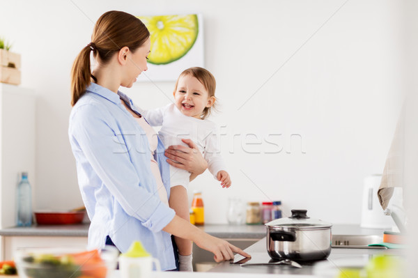 happy mother and baby cooking at home kitchen Stock photo © dolgachov