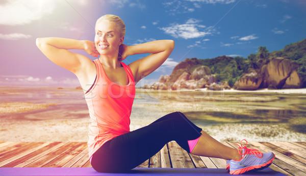 smiling woman exercising on mat outdoors Stock photo © dolgachov