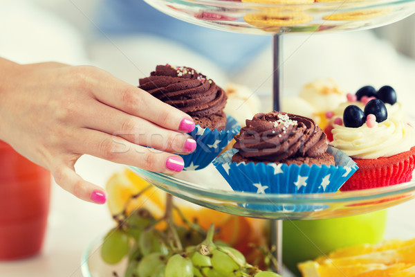 close up of hand taking cupcake from cake stand Stock photo © dolgachov