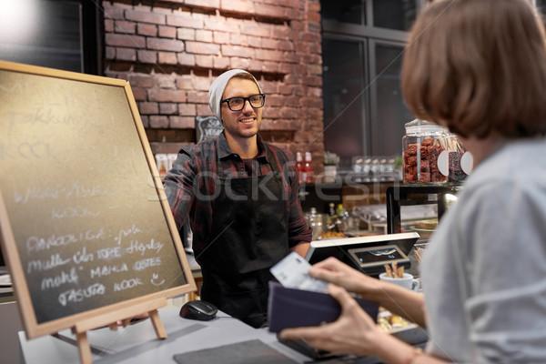 happy barman and woman paying money at cafe Stock photo © dolgachov