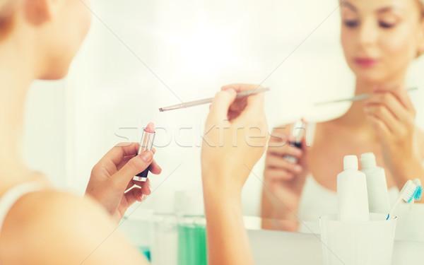woman with lipstick and make up brush at bathroom Stock photo © dolgachov