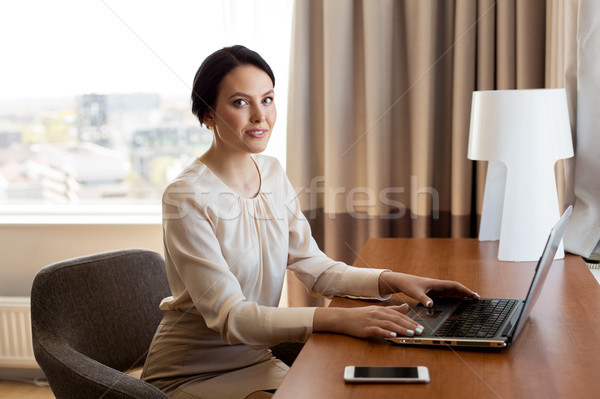 Stock photo: businesswoman typing on laptop at hotel room