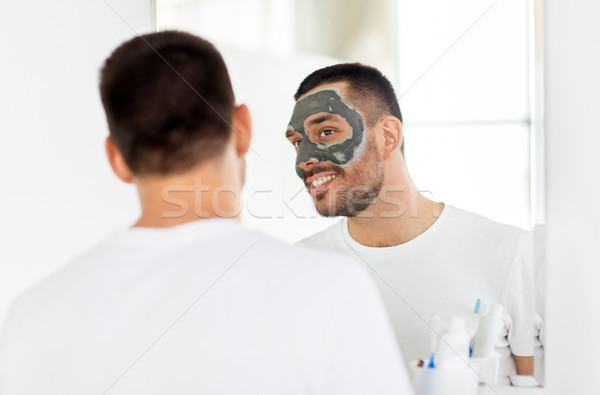 young man with clay mask on face at bathroom Stock photo © dolgachov