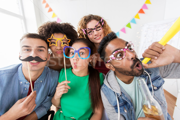 happy friends or team having fun at office party Stock photo © dolgachov