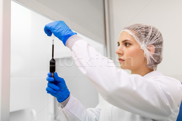 woman with sulphuric acid in dropper at laboratory Stock photo © dolgachov