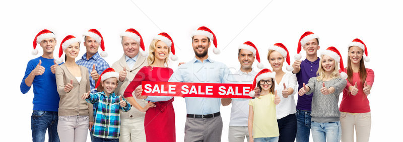 Stock photo: people in santa hats with sale sign at christmas