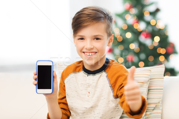 boy with smartphone at christmas showing thumbs up Stock photo © dolgachov