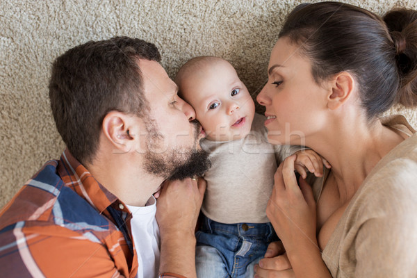 happy family lying on floor and kissing their baby Stock photo © dolgachov