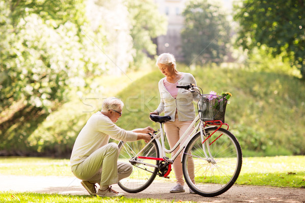 Stock photo: happy senior couple with bicycle at summer park