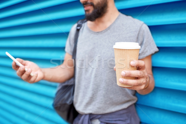 man with coffee cup and smartphone over wall Stock photo © dolgachov