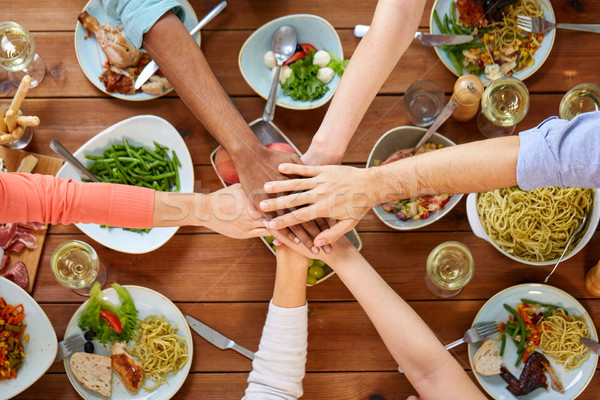 people holding hands together over table with food Stock photo © dolgachov