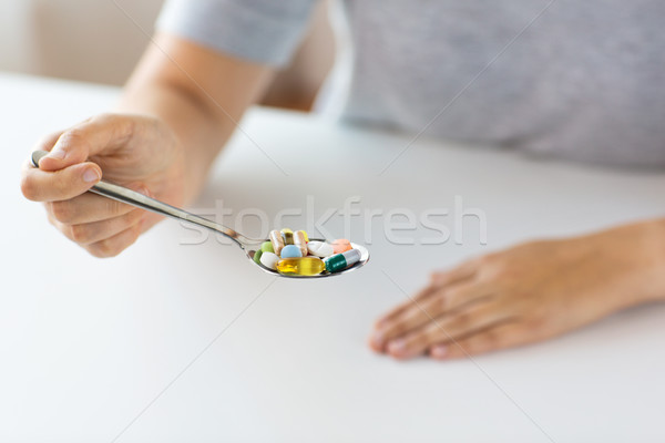 close up of female hand holding spoon with pills Stock photo © dolgachov
