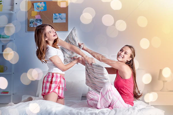 happy teen girl friends fighting pillows at home Stock photo © dolgachov