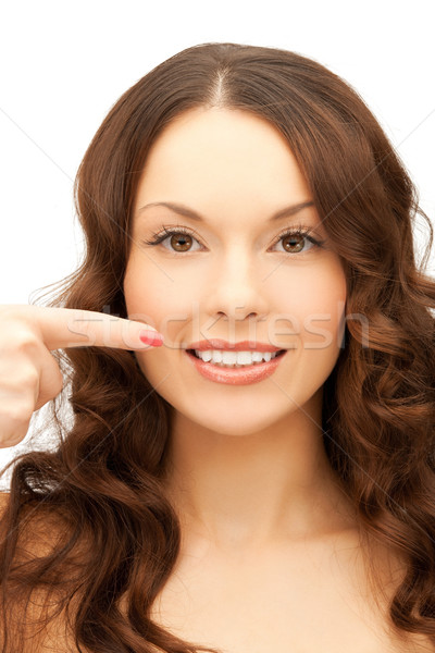 woman pointing at her toothy smile Stock photo © dolgachov