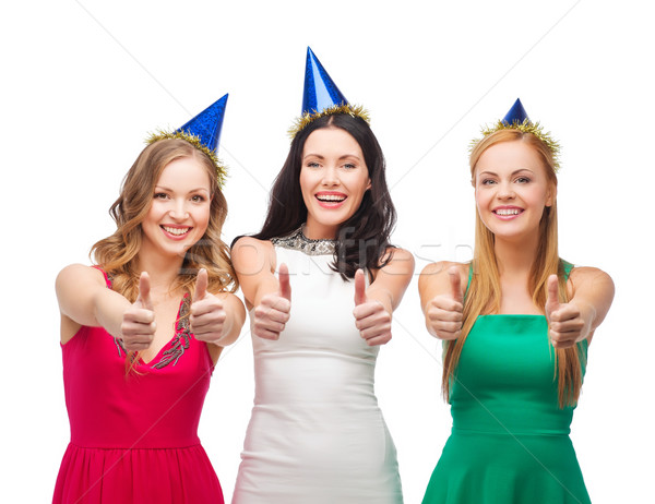 three women wearing hats and showing thumbs up Stock photo © dolgachov