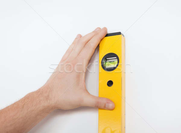 close up of male with spirit level mesuring wall Stock photo © dolgachov