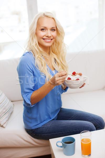 smiling woman with bowl of muesli having breakfast Stock photo © dolgachov