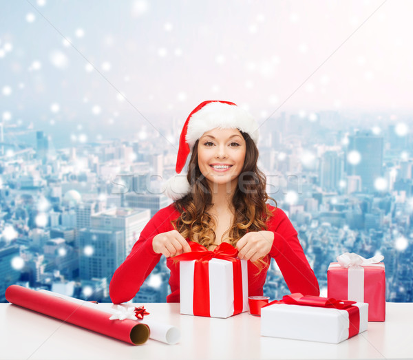 smiling woman in santa helper hat packing gifts Stock photo © dolgachov