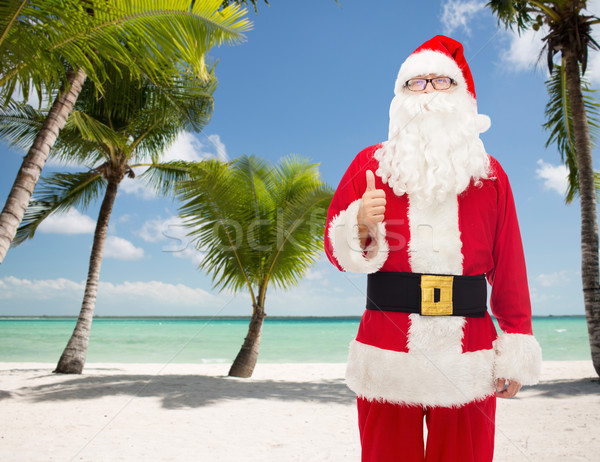 man in costume of santa claus showing thumbs up Stock photo © dolgachov