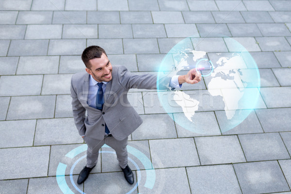 smiling businessman with globe projection outdoors Stock photo © dolgachov