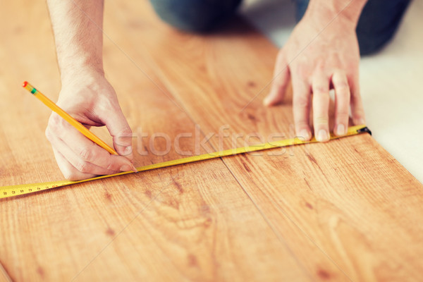 close up of male hands measuring wood flooring Stock photo © dolgachov