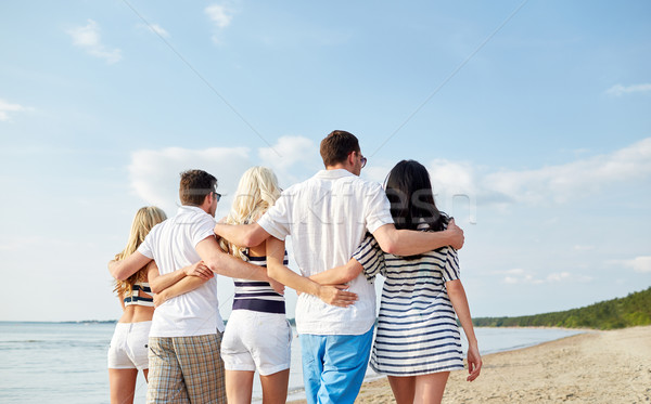 smiling friends hugging and walking on beach Stock photo © dolgachov