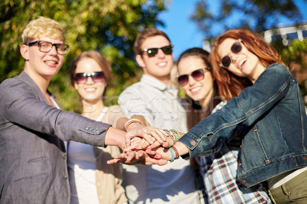 close up of teenage friends with hands on top Stock photo © dolgachov