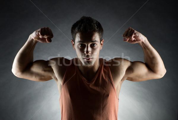 young man showing biceps Stock photo © dolgachov