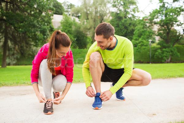 Glimlachend paar schoenveters buitenshuis fitness sport Stockfoto © dolgachov
