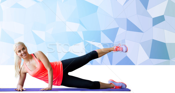 smiling woman exercising on mat over low poly Stock photo © dolgachov