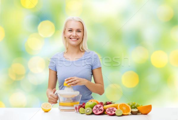smiling woman squeezing fruit juice Stock photo © dolgachov