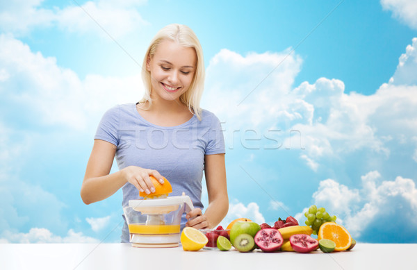 smiling woman squeezing fruit juice over sky Stock photo © dolgachov