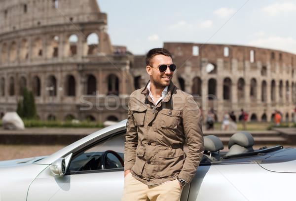 happy man near cabriolet car over coliseum Stock photo © dolgachov