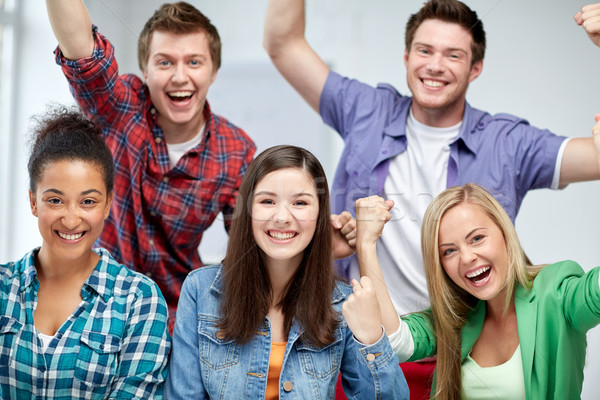 group of happy students making triumph gesture Stock photo © dolgachov
