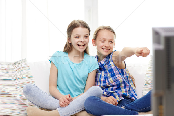 two happy little girls watching tv at home Stock photo © dolgachov