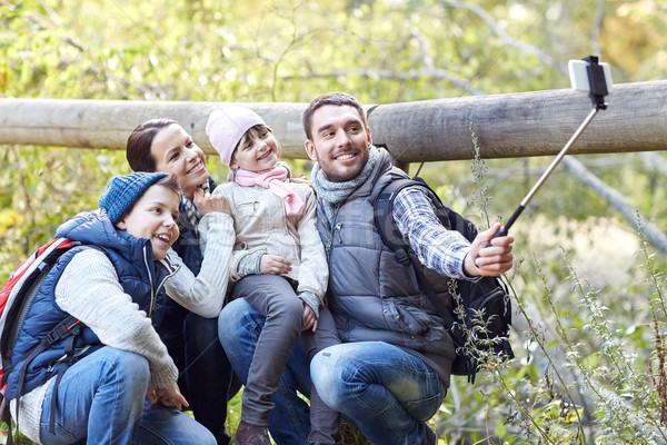 happy family with smartphone selfie stick in woods Stock photo © dolgachov
