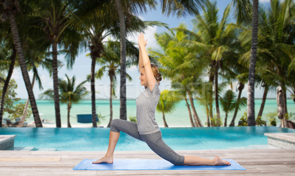 happy woman making yoga in low lunge over beach Stock photo © dolgachov
