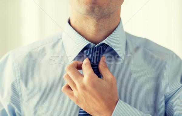close up of man in shirt adjusting tie on neck Stock photo © dolgachov