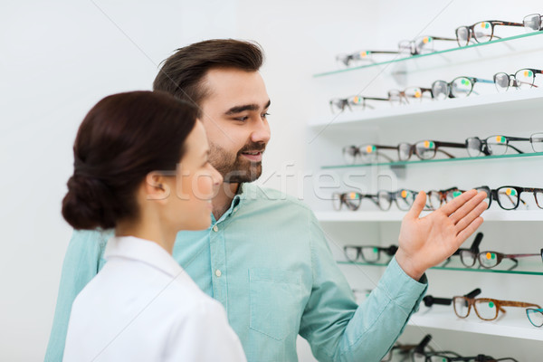 optician and man choosing glasses at optics store Stock photo © dolgachov
