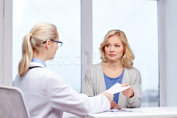 doctor giving prescription to woman at hospital Stock photo © dolgachov